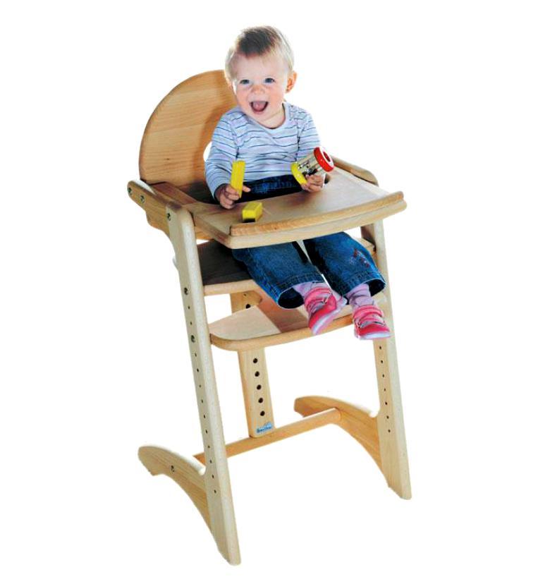ребёнок играет за деревянным стульчиком для кормления