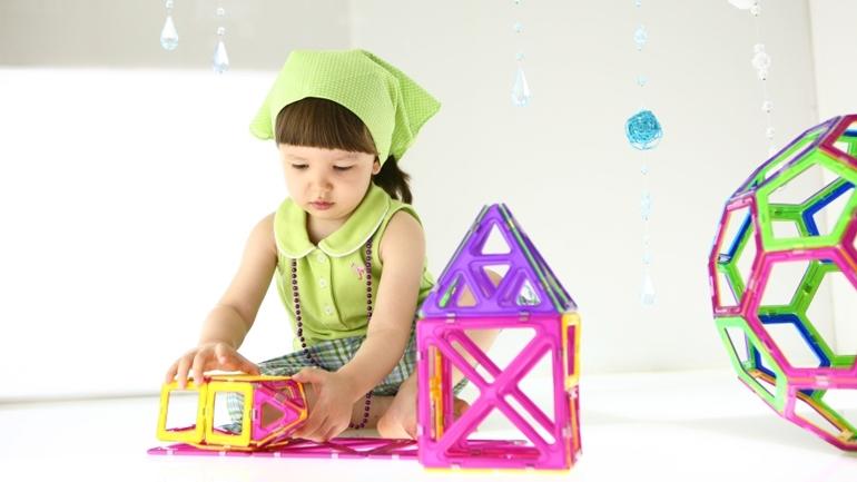 девочка играет с магнитным конструктором Magformers