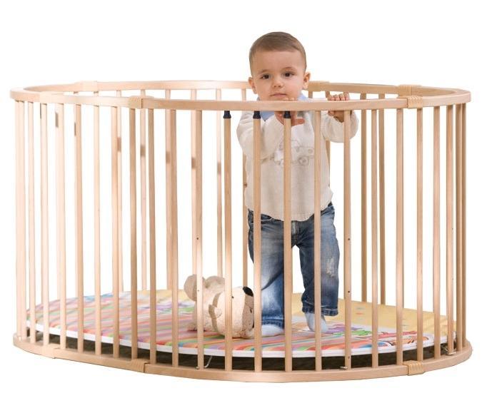 малыш в деревянном манеже
