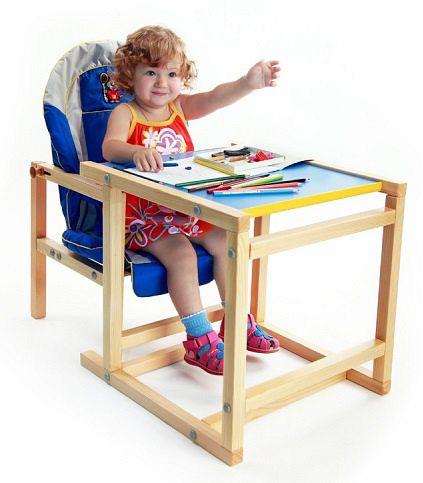 девочка за деревянным стульчиком для кормления
