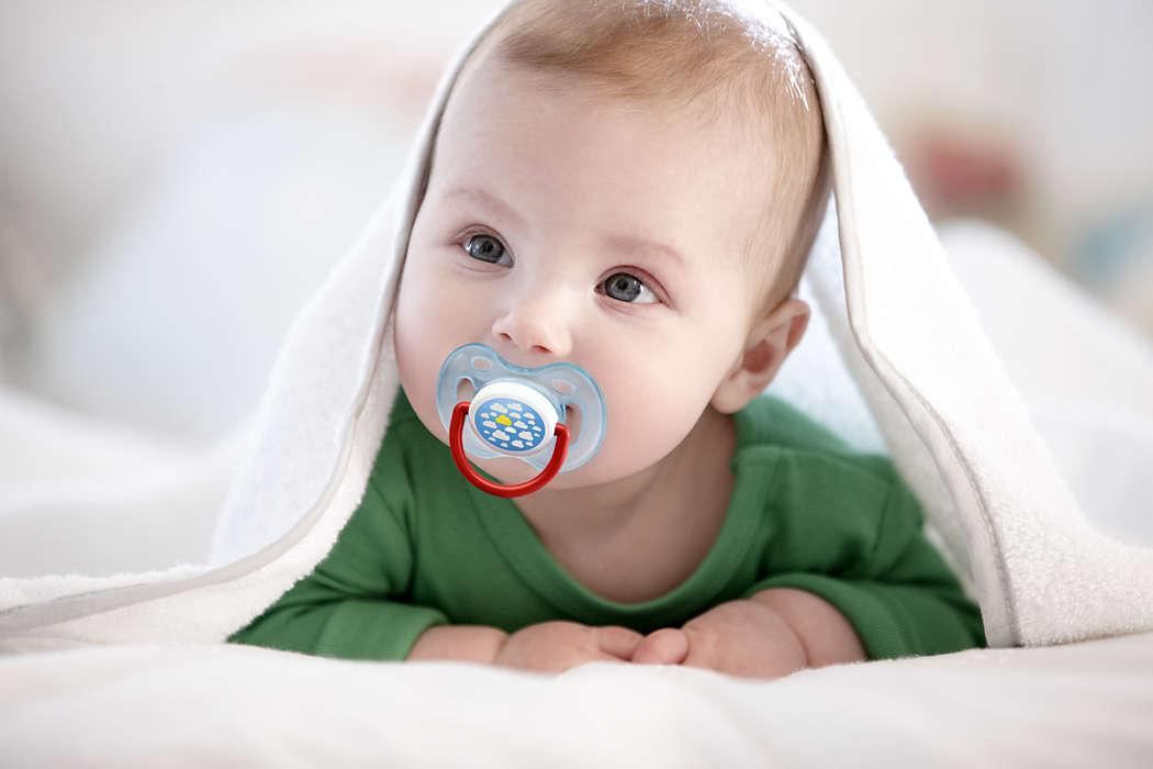 малыш с пустышкой под одеялом