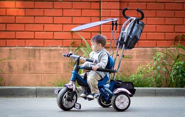 ребёнок на трёхколёсном велосипеде с ручкой
